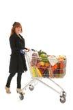 Mulher com o mantimento completo da leiteria do carrinho de compras Fotografia de Stock