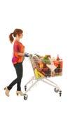 Mulher com o mantimento completo da leiteria do carrinho de compras Imagem de Stock