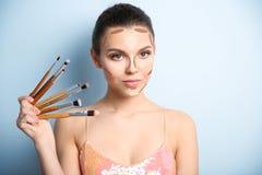 Mulher com o mapa de contorno facial da composição e escovas no fundo da cor fotografia de stock