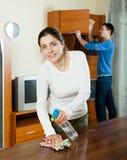 Mulher com o marido que limpa o furiture de madeira Imagens de Stock Royalty Free