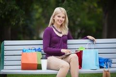 Mulher com o PC dos sacos e da tabuleta de compra ao ar livre fotografia de stock