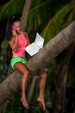 Mulher com o portátil assentado em uma árvore Imagens de Stock