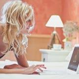 Mulher com o portátil no quarto Fotografia de Stock