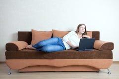 Mulher com o portátil no sofá fotos de stock
