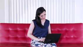Mulher com o portátil no sofá vermelho em casa filme
