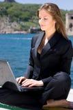 Mulher com o portátil perto do mar fotografia de stock royalty free