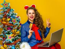 A mulher com o portátil que mostra o cartão de crédito e a vitória gesticulam Fotografia de Stock
