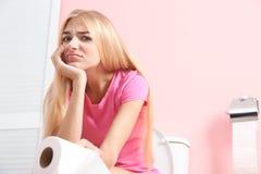 Mulher com o rolo de papel que senta-se na bacia de toalete foto de stock