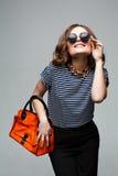 Mulher com o saco alaranjado no estúdio óculos de sol, Foto de Stock