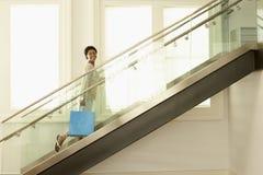 Mulher com o saco de compras em escadas de vidro modernas imagens de stock