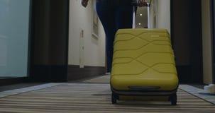 Mulher com o saco do trole que procura a sala no hotel