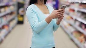 Mulher com o smartphone no supermercado ou na loja vídeos de arquivo