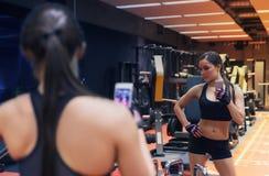 Mulher com o smartphone que toma o selfie do espelho no gym Fotografia de Stock Royalty Free