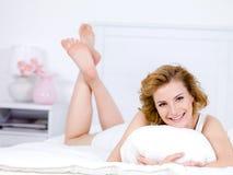 Mulher com o sorriso feliz que encontra-se em uma cama em casa Fotografia de Stock Royalty Free