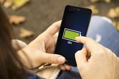 Mulher com o telefone completo da bateria no parque Foto de Stock