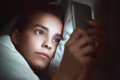Mulher com o telefone na cama, noite imagem de stock