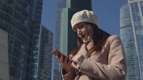 Mulher com o telefone no fundo de construções altas de uma megalópole Imagens de Stock Royalty Free