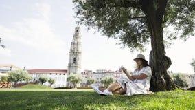 Mulher com o telefone que senta-se na máscara da árvore filme