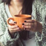 Mulher com o tratamento de mãos bonito que guarda um copo alaranjado do cacau Imagens de Stock Royalty Free