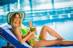 Mulher com o vidro de cocktail que refrigera perto da piscina em uma cadeira de plataforma imagens de stock royalty free