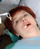 Mulher com olhar aberto da boca em seu dente do extrato Imagem de Stock