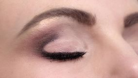 A mulher com olhos azuis bonitos e as pestanas pretas longas e brilhantes fazem, lentes de contato, fim acima, movimento lento filme