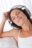 Mulher com olhos fechados que aprecia a música fotografia de stock