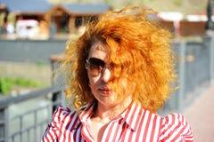 Mulher com os óculos de sol vestindo do cabelo vermelho Foto de Stock Royalty Free