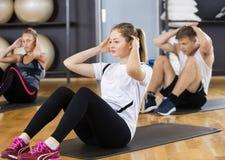 Mulher com os amigos que fazem o Situps no Gym Fotografia de Stock