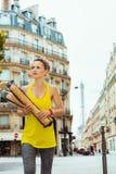 Mulher com os 2 baguettes franceses que cruzam a rua em Paris, Fran?a fotos de stock royalty free