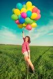 Mulher com os balões do brinquedo no campo da mola Foto de Stock