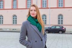 Mulher com os bordos vermelhos que olham ao lado no outono no cit Imagens de Stock Royalty Free