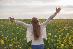 Mulher com os braços abertos no campo de trigo verde na manhã Imagens de Stock