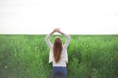 Mulher com os braços abertos no campo de trigo verde na manhã Foto de Stock Royalty Free