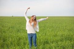 Mulher com os braços abertos no campo de trigo verde na manhã Fotografia de Stock