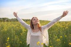 Mulher com os braços abertos no campo rapseed verde na manhã Fotografia de Stock Royalty Free
