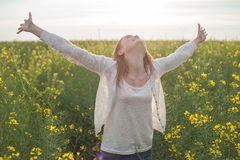 Mulher com os braços abertos no campo rapseed verde na manhã Fotos de Stock
