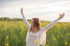 Mulher com os braços abertos no campo rapseed verde na manhã Imagem de Stock