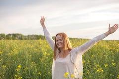 Mulher com os braços abertos no campo rapseed verde na manhã Imagem de Stock Royalty Free