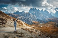Mulher com os braços acima aumentados e as montanhas majestosas no por do sol imagens de stock
