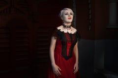 Mulher com os colmilhos de um vampiro imagem de stock