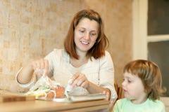 Mulher com os cookis da criança na cozinha Imagem de Stock Royalty Free