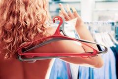 Mulher com os dois ganchos de roupa na mão na loja Fotos de Stock Royalty Free