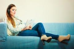 Mulher com os fones de ouvido da tabuleta que sentam-se no sofá Fotografia de Stock Royalty Free