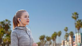 Mulher com os fones de ouvido que correm sobre a praia de Veneza imagens de stock