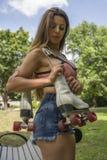 Mulher com os patins de rolo no ombro imagens de stock