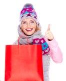 A mulher com os polegares das mostras dos sacos de compras levanta o sinal Foto de Stock