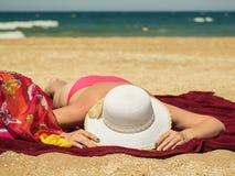 Mulher com os pregos bonitos que guardam seu banho de sol do chapéu na praia pelo mar foto de stock