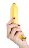Mulher com os pregos vermelhos que guardam a banana Imagens de Stock Royalty Free