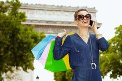 Mulher com os sacos de compras coloridos que falam em um smartphone imagens de stock